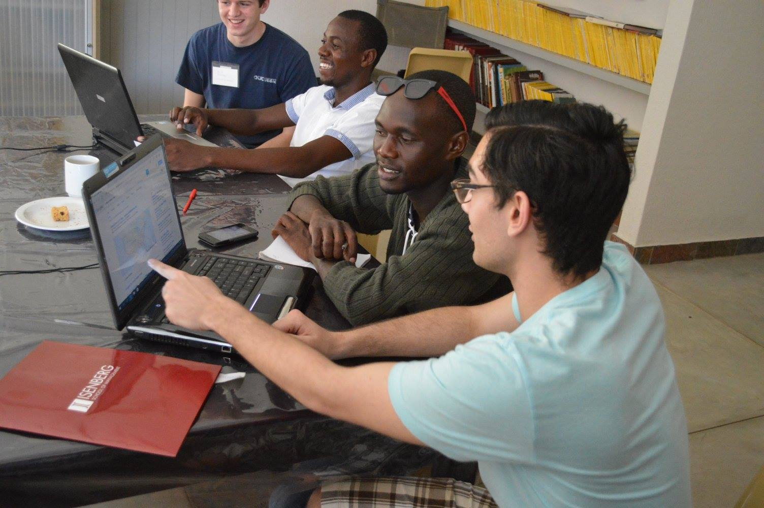 An Isenberg student instructs a South African student on the computer
